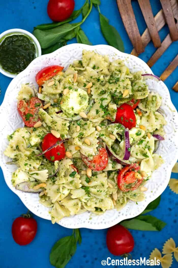 Caprese pasta salad with tomatoes and pesto sauce.