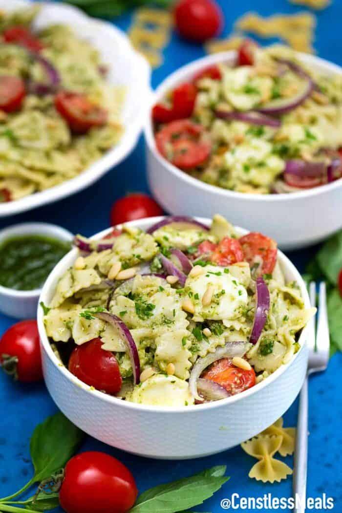 Caprese pasta salad in white bowls.