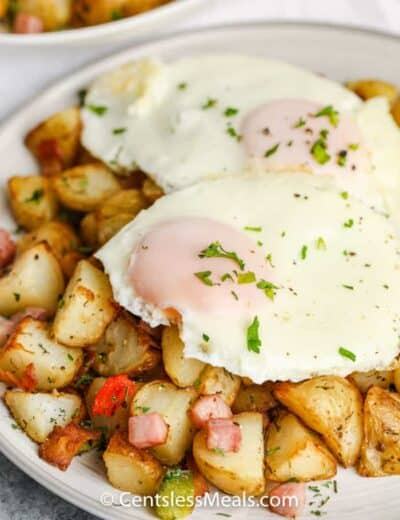 Air Fryer Home Fries on a plate topped with eggs and garnished with fresh parsley