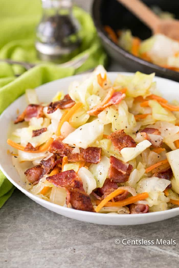 Fried cabbage and bacon in a white serving bowl with the pan in the background