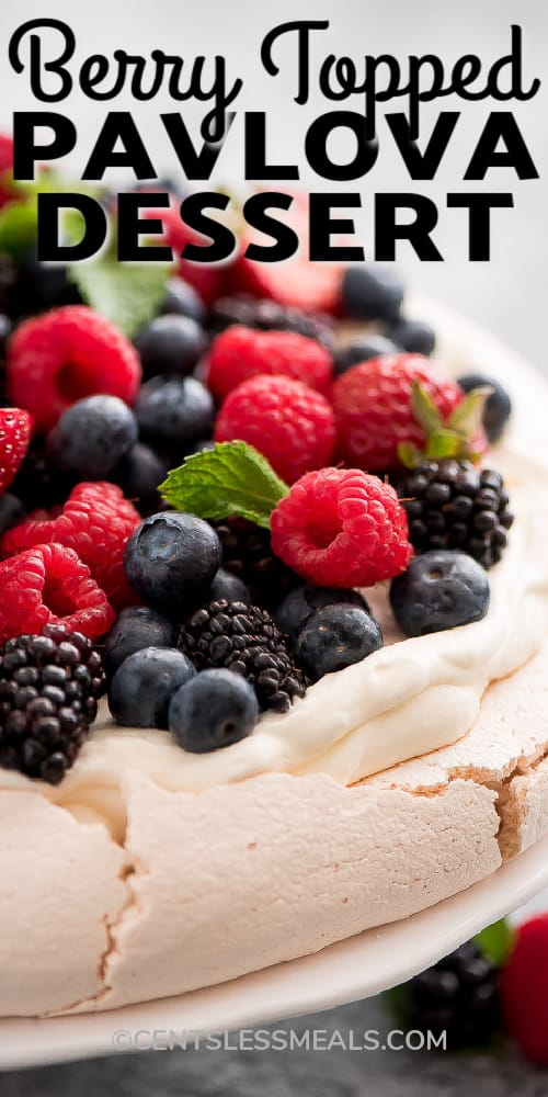 Pavlova topped with berries on a white plate with berries garnished with mint leaves with a title.