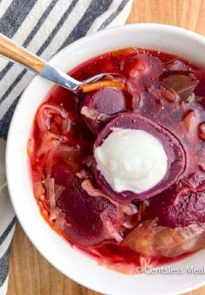 Beet Borscht served in a white bowl with a dollop of sour cream on the top.