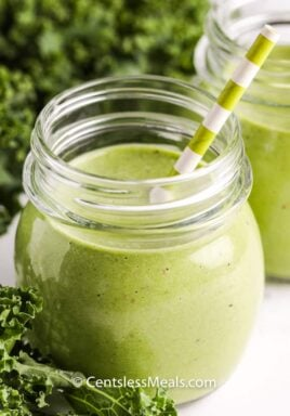 healthy Green Smoothie in a glass with greens in the background