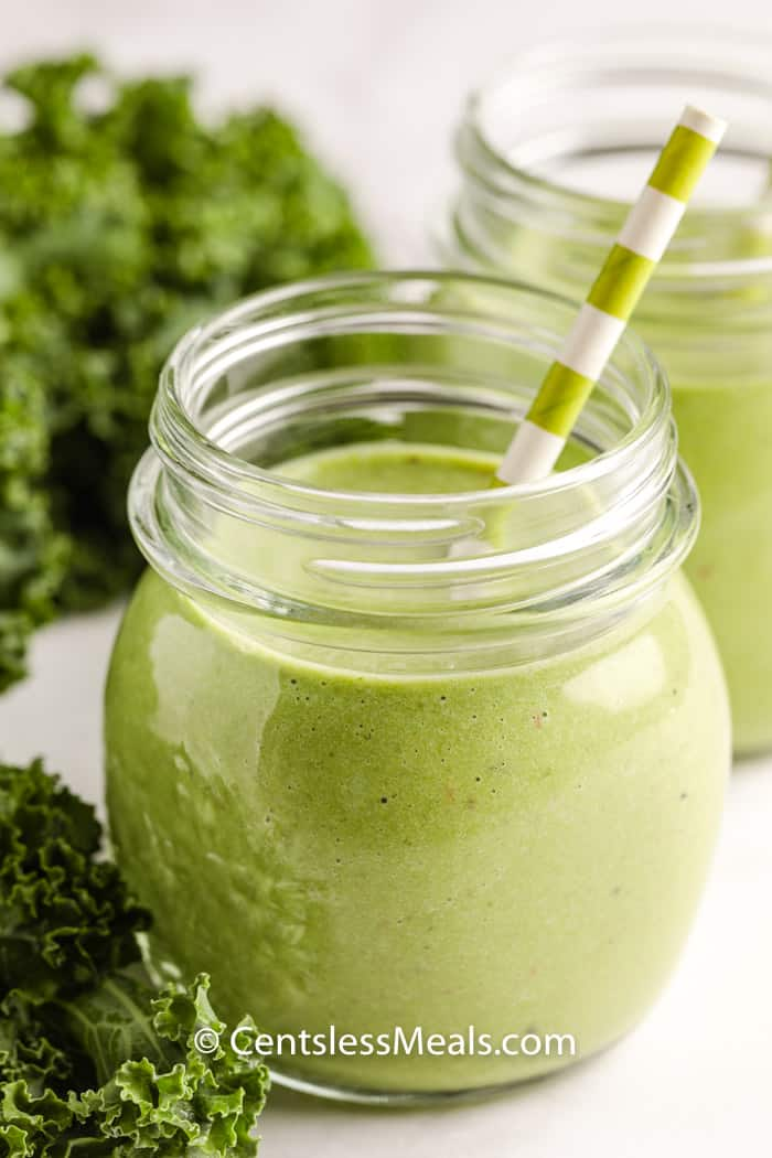 healthy Green Smoothie in glasses with a straw