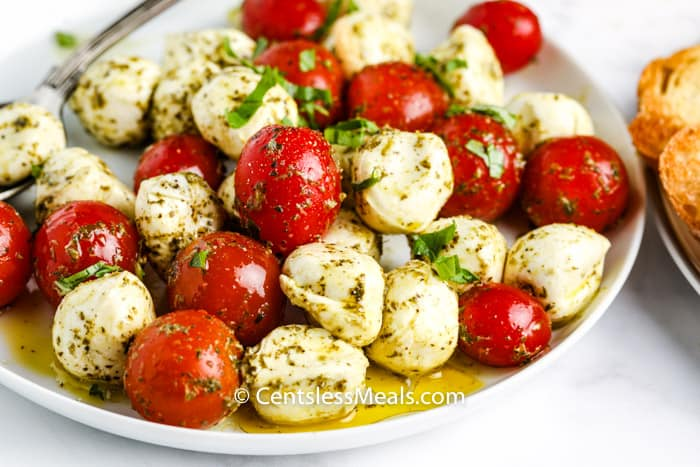 Pesto Caprese Salad on a white plate with a spoon