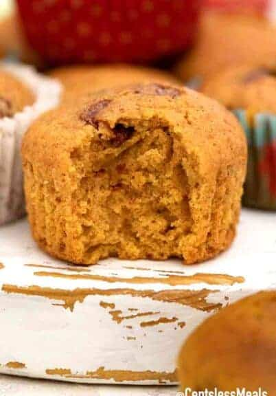 a chocolate chip pumpkin muffin with a bite taken out of it.