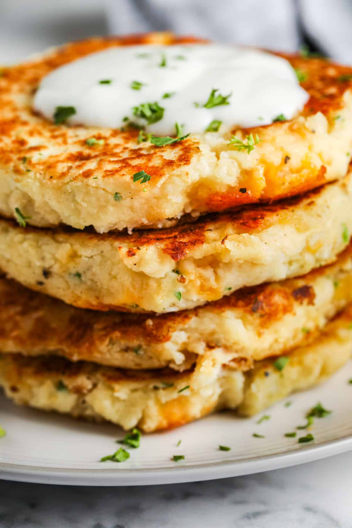 close up of Loaded Mashed Potato Pancakes stacked on a white plate with garnish and dip on top