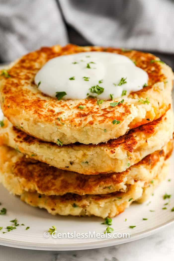 four Loaded Mashed Potato Pancakes on a plate with dip on top