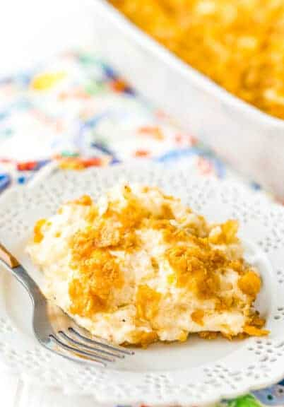 Funeral potatoes on a white plate with a fork
