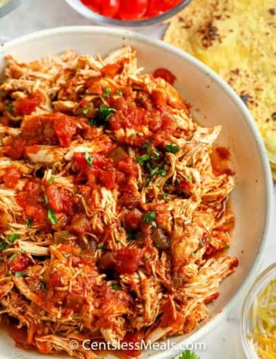 salsa chicken shredded in a bowl with ingredients around the bowl to make Crock Pot Chicken Tacos