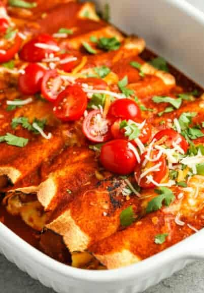 close up of cooked Chicken Enchiladas in a casserole dish