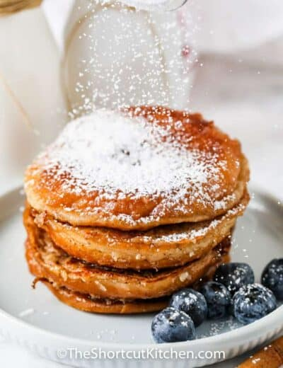shaking powder sugar on top of Glazed Donut French Toast