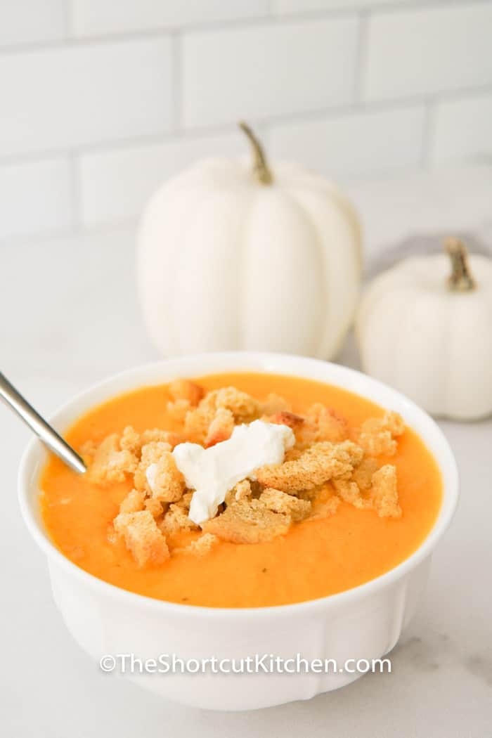 Creamy Butternut Squash Soup in a bowl with decorative pumpkins in the back