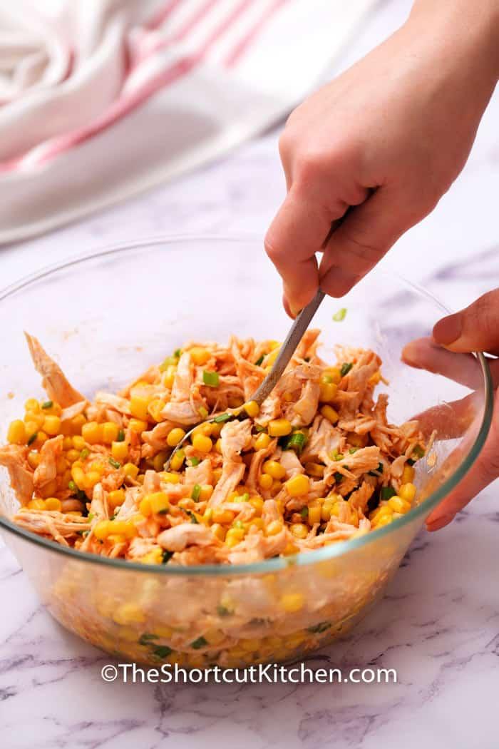 mixing ingredients to make filling for Southwest Shredded Chicken Enchiladas