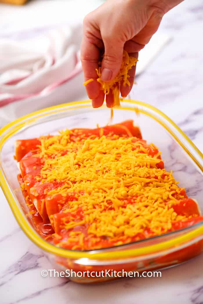 sprinkling cheese on Southwest Shredded Chicken Enchiladas