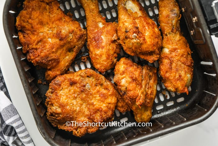 close up of chicken in the air fryer to show How to Reheat Fried Chicken in the Air Fryer