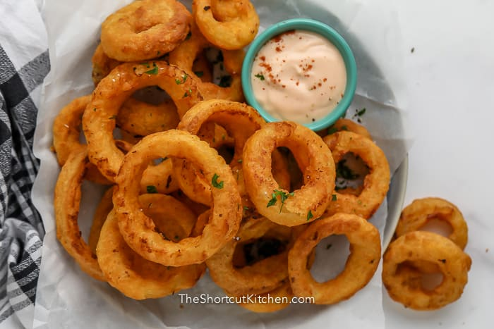Air Fryer Frozen Onion Rings in a parchment lined dish with a side of dipping sauce