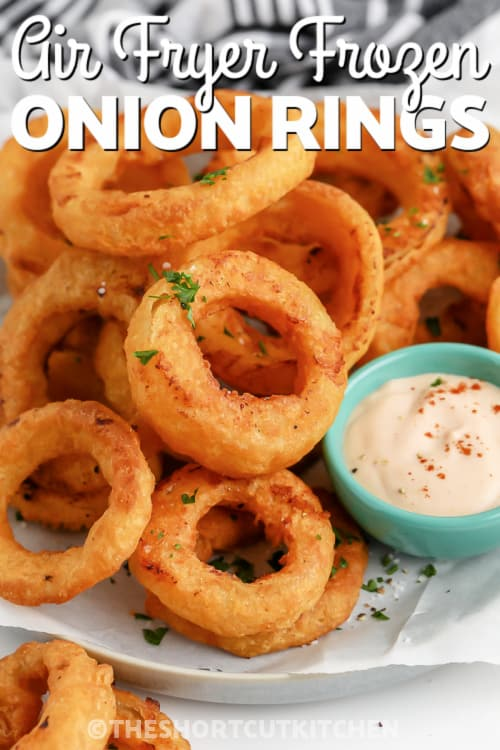 Air Fryer Frozen Onion Rings piled on a plate with a side of dipping sauce with writing