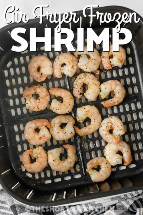 Air Fryer Frozen Shrimp in the bottom of an Air Fryer basket with a title