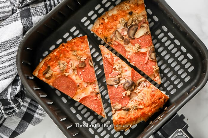 Pizza in an Air Fryer basket prior to being reheated