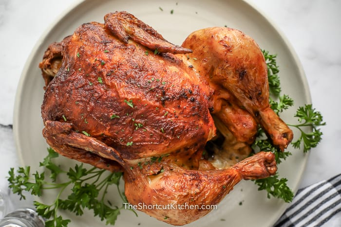 cooked rotisserie chicken on a white plate