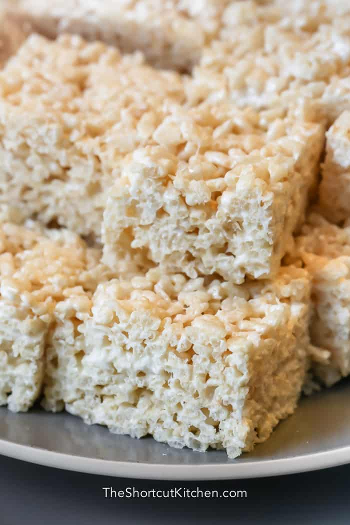 close up shot of rice krispie treats on a grey plate