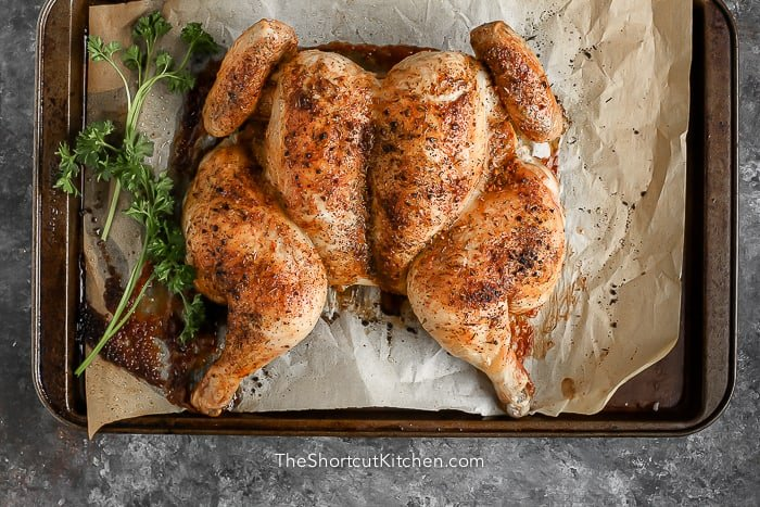 whole cooked chicken on tray with parsley