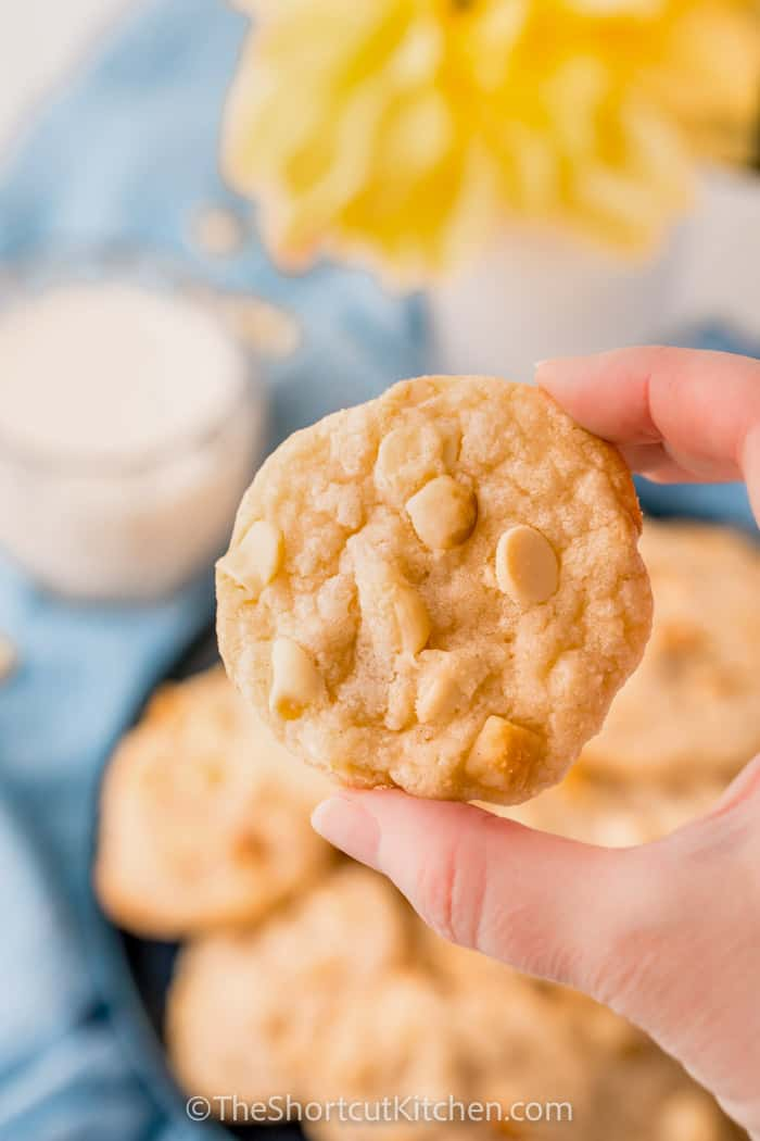 close up of White Chocolate Macadamia Nut Cookie Recipe with a plate full in the back