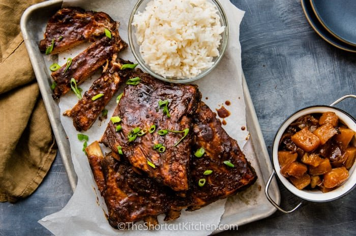 Sweet and spicy crock pot ribs on a baking tray with a side of rice