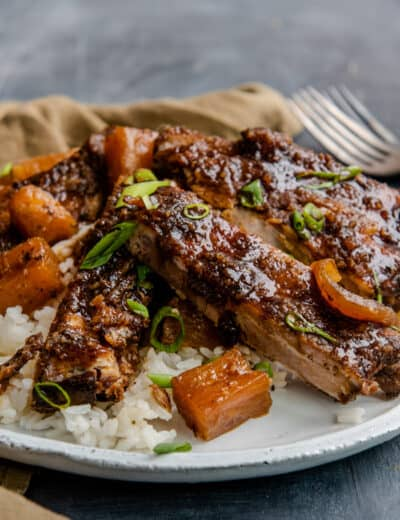 Sweet and spicy crock pot ribs plated with rice.