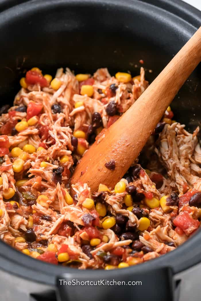 wooden spoon mixing shredded chicken with other ingredients in Crockpot