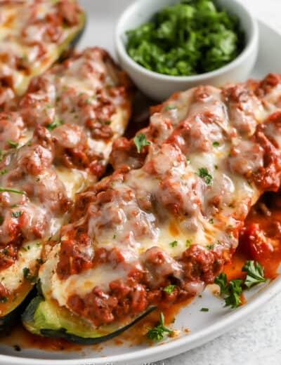 lasagna stuffed zucchini boats on a white plate