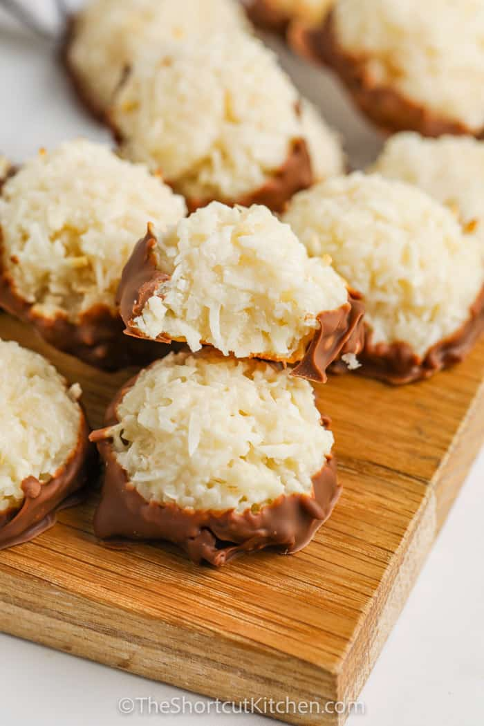 pile of Coconut Macaroons on a wooden board with a bite taken out of one