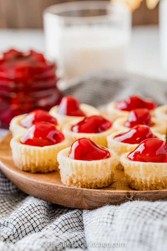 close up of Mini Cheesecake Bites with glass of milk in the back