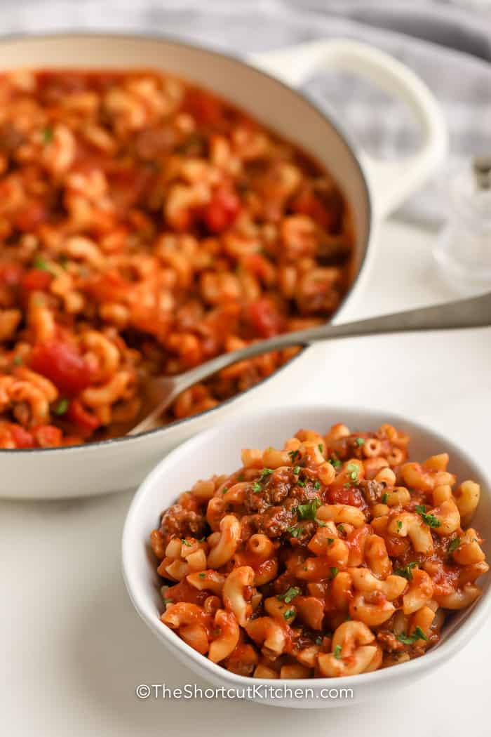 American Goulash served in a white bowl, with a white pan in the background,