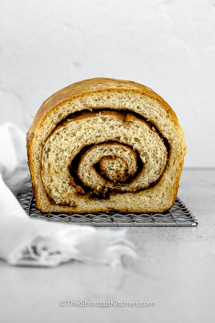 a loaf of baked Cinnamon Swirl Bread with a slice missing