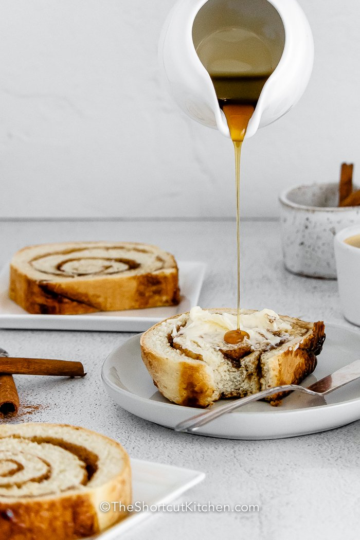 A slice of Cinnamon Swirl Bread with syrup being poured onto it