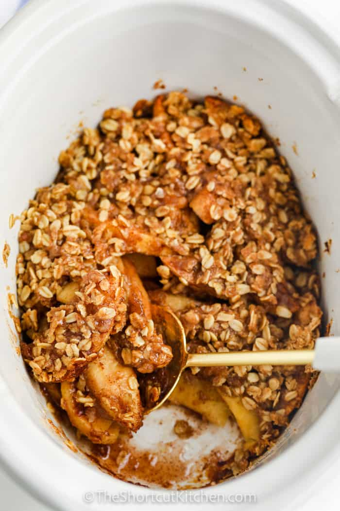 cooked Crock Pot Apple Crisp with a spoon