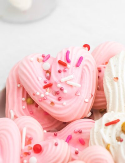 close up of pink and white Heart Meringues with sprinkles