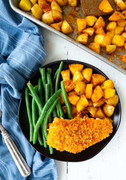 chicken, potatoes and green beans on a plate next to a blue napkin