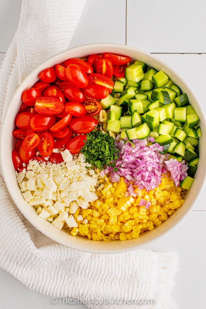 chopped up ingredients in a bowl to make an Orzo Pasta Salad