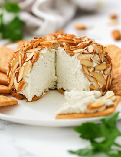 Parmesan Ranch Cheeseball with a slice taken out and crackers