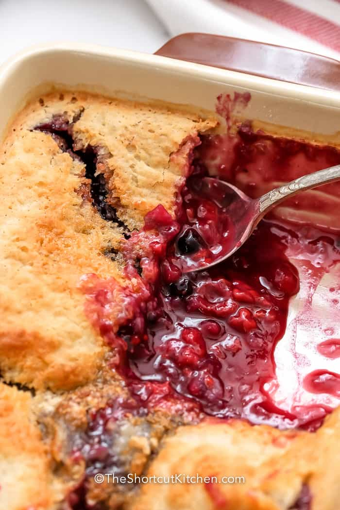 spoon scooping Mixed Berry Dump Cake in a dish