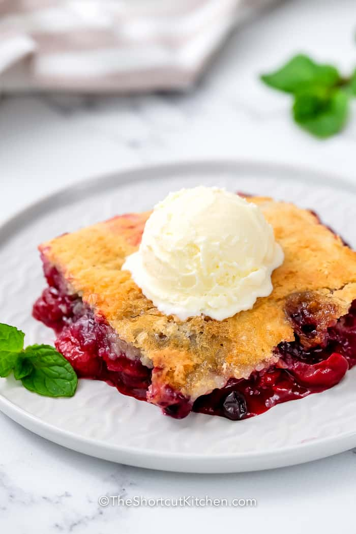 Mixed Berry Dump Cake on a plate topped with ice cream